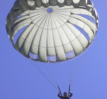 Airborne Systems MC-6 Army Troop Parachute non-steerable for military jumpers. Low opening. Carries up to 400 lbs. Minimum deployment altitude 500 ft. Canopy and jumper from below close up with blue sky.
