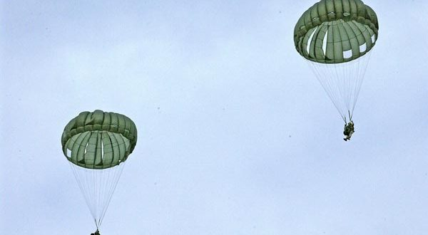 Airborne Systems MC-6 Army Troop Parachute non-steerable for military jumpers. Low opening. Carries up to 400 lbs. Minimum deployment altitude 500 ft. Two deployed canopies and jumpers from a distance with blue sky and light clouds.