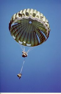 Airborne Systems MC-6 Army Troop Parachute non-steerable for military jumpers. Low opening. Carries up to 400 lbs. Minimum deployment altitude 500 ft. Canopy and jumper with blue sky.