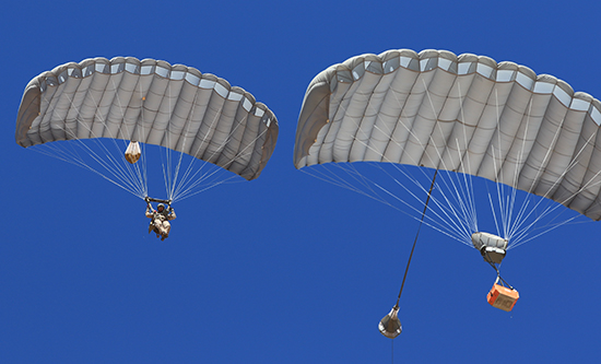Airborne Systems Combo Drop MicroFly II Army Cargo delivery system. JPADS / GPADS: Guided Precision Aerial Delivery System. Use with any Airborne Systems Ram Air Canopy. Troop jumper and cargo parachutes from below with blue sky.