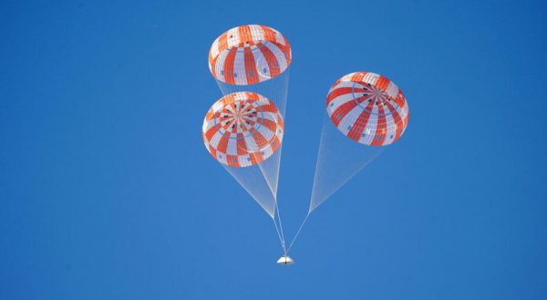 Airborne Systems - Space recovery parachutes systems. Inflatable flotation devices and landing systems. Capsule, booster, and payload recovery systems for spacecraft equipment. Space capsule descending with 3 red and white canopies and blue sky.