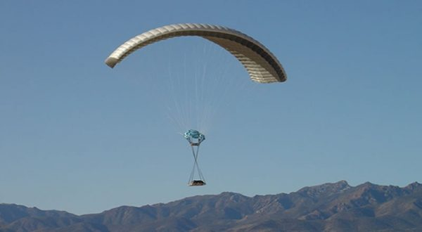Airborne Systems DragonFly Army Cargo Delivery Parachute System flying with cargo. JPADS 10K System of Choice. Eliptical canopy carries loads up to 10,000 lbs. Max altitude 24,500 ft. View of canopy and payload from the side with mountains behind.