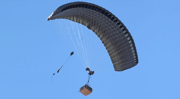 Airborne Systems DragonFly Army Cargo Delivery Parachute System flying with cargo. JPADS 10K System of Choice. Eliptical canopy carries loads up to 10,000 lbs. Max altitude 24,500 ft. View of canopy and payload from below.