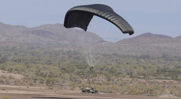 Airborne Systems DragonFly Army Cargo Delivery Parachute System landing with army vehicle payload. JPADS 10K System of Choice. Eliptical canopy carries loads up to 10,000 lbs. Max altitude 24,500 ft.