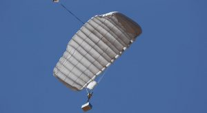 Airborne Systems Canopy with payload. FC Mini Army cargo delivery parachute system. JPADS / GPADS: Guided Precision Aerial Delivery System. Carries 200-500 lbs. Max deployment altitude 24,500 ft. Deployed canopy with blue cargo box and blue sky.