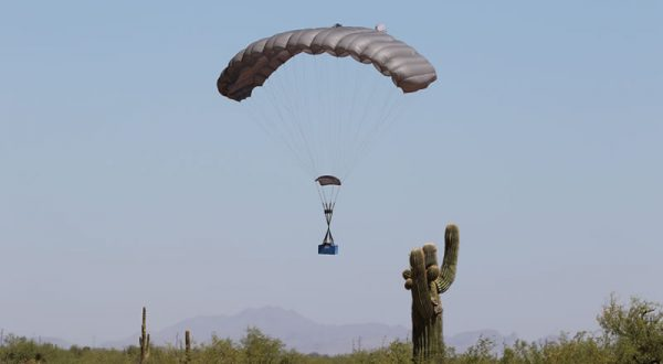 Airborne Systems Canopy with payload landing in desert with cactus in foreground, mountains in background. FC Mini Army cargo delivery parachute system. JPADS / GPADS: Guided Precision Aerial Delivery System. Carries 200-500 lbs. Max deployment altitude 24,500 ft