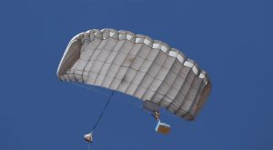 Airborne Systems Canopy with payload. FC Mini Army cargo delivery parachute system. JPADS / GPADS: Guided Precision Aerial Delivery System. Carries 200-500 lbs. Max deployment altitude 24,500 ft. Deployed canopy from below with blue cargo box and blue sky.