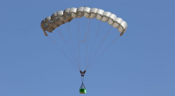 Airborne Systems Canopy with payload. FC Mini Army cargo delivery parachute system. JPADS / GPADS: Guided Precision Aerial Delivery System. Carries 200-500 lbs. Max deployment altitude 24,500 ft. Deployed canopy with green cargo box with blue sky.