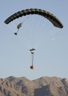 Airborne Systems FireFly Army Cargo Delivery Parachute System. JPADS 2K System of Choice. Carries unmanned loads up to 2,200 lbs. Max deployment altitude 24,500 ft. mountains. Deployed canopy with orange cargo box, mountains and blue sky.