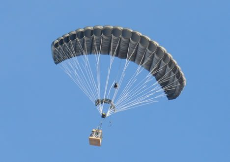 Airborne Systems FireFly Army Cargo Delivery Parachute System. JPADS 2K System of Choice. Carries unmanned loads up to 2,200 lbs. Max deployment altitude 24,500 ft. Deployed canopy with cargo box and blue sky.