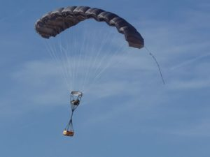 Airborne Systems FireFly Army Cargo Delivery Parachute System. JPADS 2K System of Choice. Carries unmanned loads up to 2,200 lbs. Max deployment altitude 24,500 ft. drop. Deployed canopy with orange cargo box, blue sky and whispy clouds.