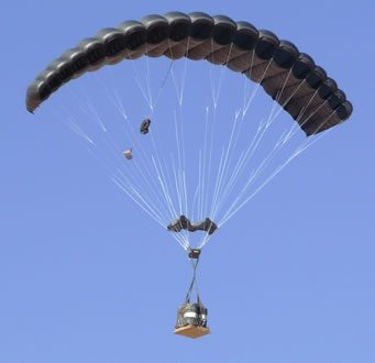 Airborne Systems FireFly Army Cargo Delivery Parachute System. JPADS 2K System of Choice. Carries unmanned loads up to 2,200 lbs. Max deployment altitude 24,500 ft. Deployed canopy with cargo on platform and blue sky.