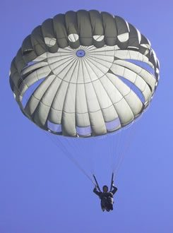 Airborne Systems MC-6 Army Troop Parachute non-steerable for military jumpers. Low opening. Carries up to 400 lbs. Minimum deployment altitude 500 ft. lone soldier with blue sky.