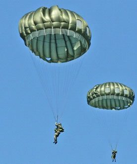 Airborne Systems MC-6 Army Troop Parachute non-steerable for military jumpers. Low opening. Carries up to 400 lbs. Minimum deployment altitude 500 ft. Two soldiers, green canopies and blue sky.