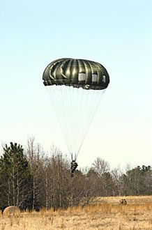Airborne Systems MC-6 Army Troop Parachute non-steerable for military jumpers. Low opening. Carries up to 400 lbs. Minimum deployment altitude 500 ft. Soldier landing near forest with green canopy.