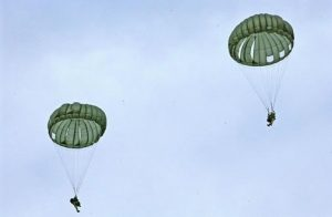 Airborne Systems MC-6 Army Troop Parachute non-steerable for military jumpers. Low opening. Carries up to 400 lbs. Minimum deployment altitude 500 ft. Two jumpers with green parachutes blue sky.