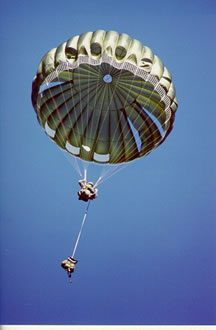 Airborne Systems. MC-6 Army Troop Parachute non-steerable for military jumpers. Low opening. Carries up to 400 lbs. Minimum deployment altitude 500 ft. Deployed canopy and cargo with blue sky