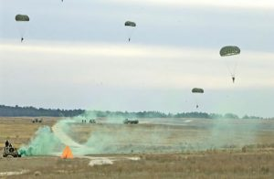 Airborne Systems MC-6 Army Troop Parachute non-steerable for military jumpers. Low opening. Carries up to 400 lbs. Minimum deployment altitude 500 ft. Desert landing five parachutes. Jeep in foreground.