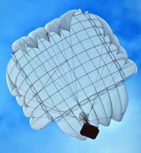 Airborne Systems Unicross Army cargo delivery parachute system. Low cost, modular design for one-time use or quick repack. Three sizes carry payloads of 75 lbs to 3,200 lbs. Cargo drop white canopy from below, blue sky. Military & space textile manufacturing & design. Army & space parachute canopies, aerial delivery (GPADS/JPADS). Aircraft & spacecraft deceleration systems.