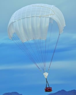 Airborne Systems Unicross Army cargo delivery parachute system. Low cost, modular design for one-time use or quick repack. Three sizes carry payloads of 75 lbs to 3,200 lbs. Cargo drop deployed white canopy and red cargo box with blue sky and mountains behind.