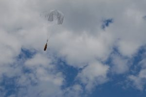 Airborne Systems Unicross Army cargo delivery parachute system. Low cost, modular design for one-time use or quick repack. Three sizes carry payloads of 75 lbs to 3,200 lbs. Cargo drop deployed canopy blue cloudy sky.
