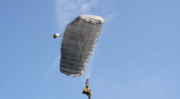 Airborne Systems - Intruder RA-1 Army Ram Air Parachute system for military special forces and beginner jumpers. Carries 450 lbs. Max deployment altitude 25,000 ft. Jumper and blue sky. Fort Bragg 2016.