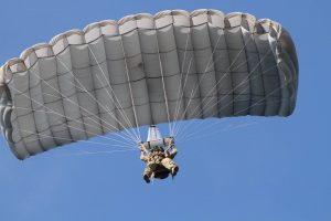 Airborne Systems - Intruder RA-1 Army Ram Air Parachute system for military special forces and beginner jumpers. Carries 450 lbs. Max deployment altitude 25,000 ft. Jumper from below with blue sky. Fort Bragg.