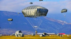 Airborne Systems - T-11 Static Line Troop Parachute System. T-11 Army Troop Parachute non-steerable for military jumpers. Carries an all-up weight of 400 lbs. Max deployment altitude of 7500 ft.Soldier landing in field with 6 other paratroopers descending to land, and mountains in background.