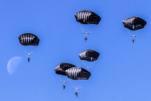 Airborne Systems T-11 Army Troop Parachute non-steerable for military jumpers. Carries an all-up weight of 400 lbs. Max deployment altitude of 7500 ft. 6 paratroopers descending freefall with blue sky and half moon.