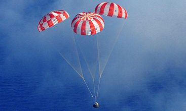 Airborne Systems space parachute & inflatable systems. Military-grade deceleration, airbag landing, aerospace recovery, personnel & cargo delivery parachute systems. Entry, Descent & Landing System (EDLS) development for space and high altitude applications. Recovery system for the Discoverer XIII reentry capsule. Three red and white canopies with blue sky.