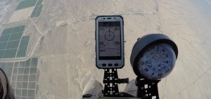 Airborne Systems jTrax Navaid parachute navigation system for army and military jumpers and JPADS and GPADS cargo guided precision aerial delivery systems. Close up of apparatus and compass pre-jump at 5,000 feet with land in background.