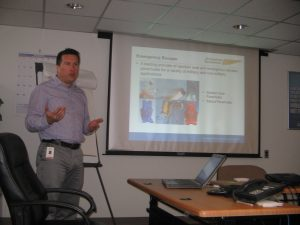 """Vincent Mignot, International Business Unit Manager at Airborne Systems teaching class for Camden Youth Aviation Program. Screen behind him reads, """"Emergency Escape; Airborne Systems. A leading provider of..."""" Military Parachute Training. Troop and cargo parachute certification for army riggers & jumpers. Instruction for oxygen and JPADS systems."""
