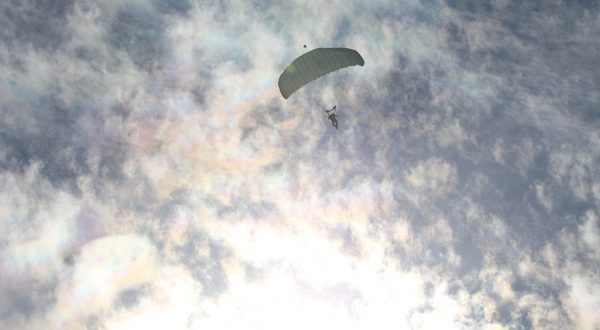 Airborne Systems outfits the USMC. Airborne Systems North America are the proud providers of the brand new Edge Multi-Mission Parachute System to the United States Marine Corps. Deployed canopy and parachutist from below and afar with blue sky and rainbow laced clouds.