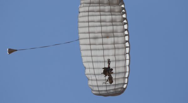 Airborne Systems Hi-5 Army Ram Air Parachute Personnel product system for military special forces jumpers with glide modulation. Carries 485 lbs. Max deployment altitude 25,000 feet. Deployed canopy and parachutist from below with blue sky.